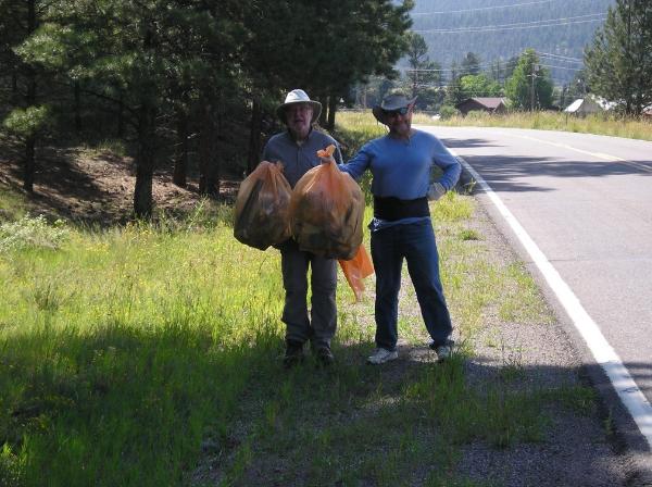 Highway Cleanup, men holding bags of trash